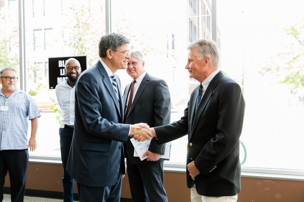 MMCDC founder Arlen Kangas shakes hands with Sec. Lew. President Kevin Shipley in background along with Seward Co-Op store manager Ray Williams.